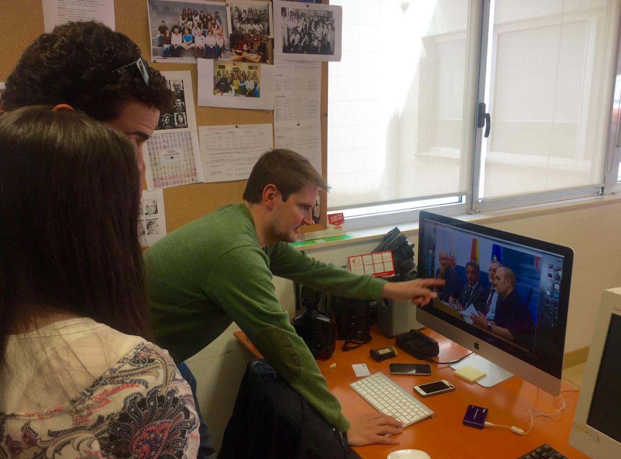 El responsable del departamento gráfica explica a los alumnos las fotos de la rueda de prensa.